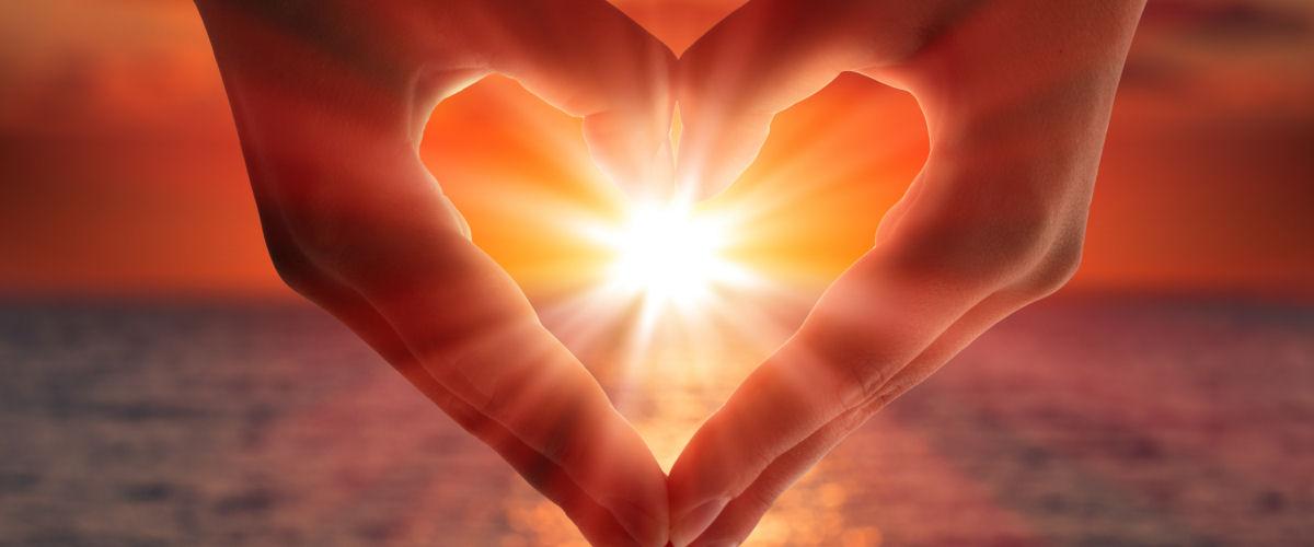 Hænder danner hjerte foran sol_slider